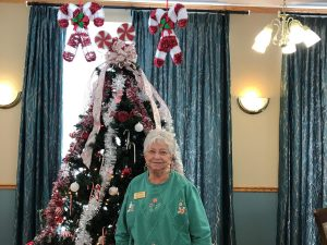 Glenda, a resident at Eagle Ridge of Decatur, stands in front of a tree at the community.