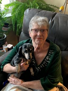 Vivian, a resident at Heritage Woods of Freeport, holds her dog while sitting in a chair at the community.
